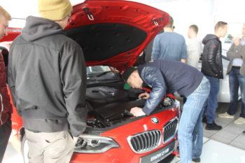 Auszubildende nehmen den Motor des BMW 218i in Augenschein. Foto: Heidrun Spenner