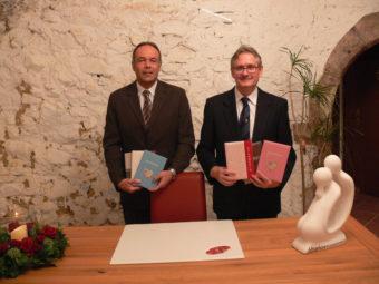 Die Standesbeamten Frank Ruhland und Ernst Kubisch (v.l.) stellen im neuen Traukeller die neuen Stammbücher der Trausaison 2016/2017 vor. Foto: Dittmer