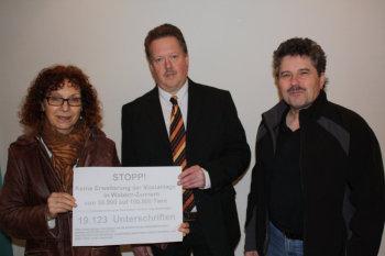 Vor der öffentlichen Sitzung  überreichten Barbara Düsterhöft und Horst Sandmüller von der BI dem Vorsitzenden der Gemeindevertretung, Wolfgang Ziegler (SPD, Mitte), symbolisch die über 19.000 Unterschriften der Tierschützer. Foto: nh