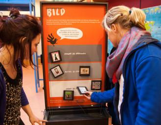 Im Lernlabor der Bildungsstätte Anne Frank sind die Verwirklichung von Menschenrechten das zentrale Thema, mit dem man sich – wie diese beiden Ausstellungsbesucherinnen – aktiv handelnd auseinandersetzen kann. Foto: nh
