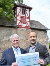 E.-Ulrich Bruckmann und Thomas Garde bei symbolischer Scheckübergabe vor der Hospitalskapelle. Foto: Reinhold Hocke