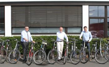 Andreas Siebert, Bürgermeister der Gemeinde Niestetal, nahm die Fahrräder von Fred-Martin Dillenberger, Leiter des Corporate Real Estate Managements und Matthias Schäpers, Referent Nachhaltigkeit bei SMA, entgegen. Foto: nh