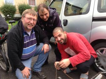 Reinhold Tripp, Alkalay Saddam und Edmooh Shdrawi reparieren eine Fahrradkette. Foto: G. Hahn