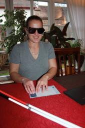 Die Teilnehmerin eines Sensiblisierungsseminars zum Thema Barrierefreies Reisen versucht, Blindenschrift zu lesen. Foto:  MosGiTo, Gisela Moser