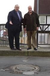 Bernd Siebert MdB und Ortsvorsteher Klaus Dieter Mirswa vor einem abgesenkten Kanaldeckel mitten auf der Fahrbahn. Foto: nh