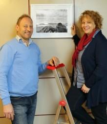 Fotograf Jürgen Becker und Iris Frech, Geschäftsführerin der Hephata-Klinik, hängen die Fotos der Ausstellung auf. Foto: nh