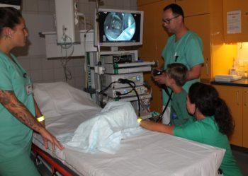 Auf der Suche: Oberarzt Mathias Noll durchleuchtet mit einem Endoskop einen mit Gummibärchen gefüllten Karton. Mit dabei waren Sophia Simshäuser (links) und Petra Weinrich (kniend rechts). Foto: nh