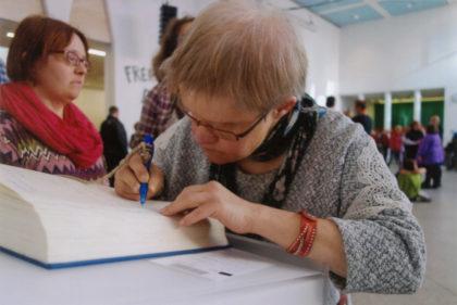 Uschi Zimmer trägt sich während der Ausstellungseröffnung in das Gästebuch ein. Im Hintergrund Claudia Simun. Foto: nh