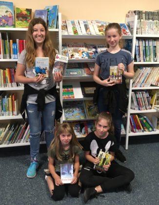Tabea Zeidler, Leni Scheffer, Julia Geiger und Leni Horstmann (von links nach rechts) freuen sich über die vielen Bücher Margrets Steenfatts, die es in der Bücherei zum Ausleihen gibt. Foto: nh