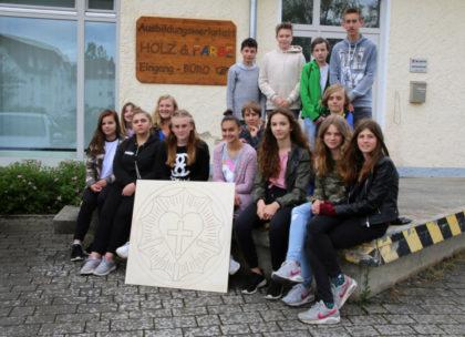 Stolz präsentieren die Konfirmanden ihre gefräste Lutherrose vor der Hephata-Holzwerkstatt in Treysa. Foto: nh
