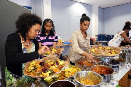Kunstvoll richten Birhan Samuel und ihre Helferinnen die Speisen auf großen Platten an, von denen gemeinsam am Tisch gegessen wird. Foto: nh