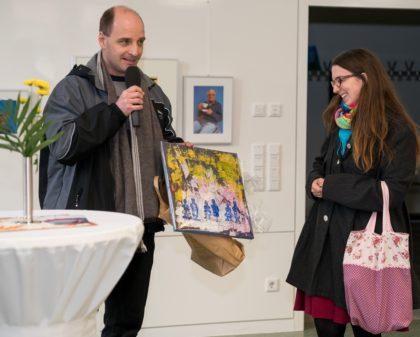 Markus Balkenhol, Mitarbeiter der Hephata-Behindertenhilfe, überreicht Julia Gilfert als Dankeschön ein Kunstwerk aus dem Atelier Farbenhaus. Foto: Hephata
