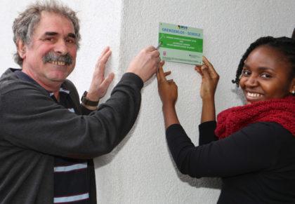 """Berufsschullehrer Horst Brixius und Gahelle Corine Ngahan Tchouga, eine der Referentinnen, haben schon einen geeigneten Platz für die Plakette gefunden, die künftig die Friedrich-Trost-Schule als """"Grenzenlos-Schule"""" auszeichnen wird. Foto: nh"""