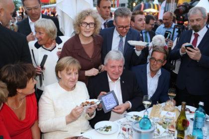 """Die Hephata-Vorstandsmitglieder Judith Hoffmann und Maik Dietrich-Gibhardt haben Bundeskanzlerin Angela Merkel beim Hessenfest in Berlin eine Für-Uns-Currywurst serviert. Ministerpräsident Volker Bouffier erklärte der Regierungschefin: """"Hephata leistet gute und wichtige Arbeit."""" Foto: nh"""