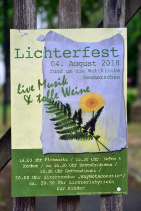 Am Kirchengatter hängt die Einladung zum Lichterfest im August. Foto: Schmidtkunz