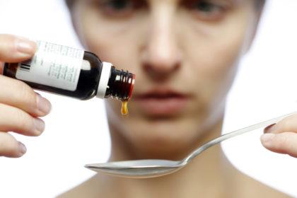 Eine Frau tropft ein flüssiges Medikament auf einen Löffel. Foto: Asklepios