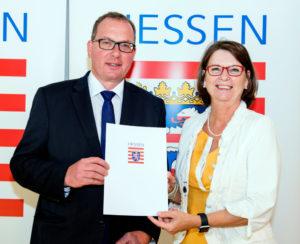 Bürgermeister Frank Börner nimmt von Landwirtschaftsministerin Priska Hinz die Urkunde für Gudensberg entgegen. Foto: Boris Borm
