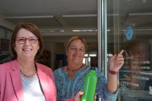 Ministerin Priska Hinz (li.) gemeinsam mit Aria van Dijk, Beraterin der Verbraucherzentrale, beim Anbringen des Refill-Aufklebers an der Verbraucherzentrale in Wiesbaden. Foto: Umweltministerium