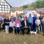 Mark Weinmeister, der hessische Europastaatssekretär, hat einen Förderbescheid an den Dorfverschönerungsverein übergeben. Foto: nh