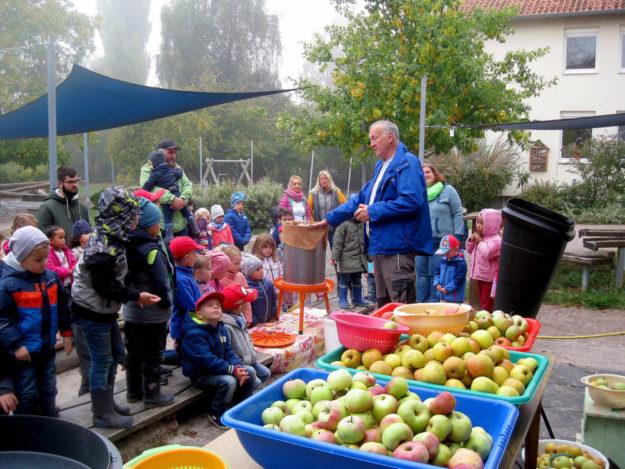 Rainer Hartmann vom NABU (re.) erklärt die Apfelsaftherstellung erst Schritt für Schritt, dann geht es in die Produktion. Foto: nh