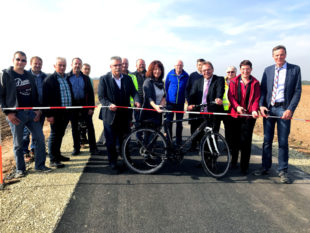 Das Flatterband wird zerschnibbelt, die Wirtschaftswege sind damit wieder für landwirtschaftlichen Verkehr, für Radfahrer und Fußgänger freigegeben. Foto: nh