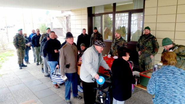Die Bürgerinnen und Bürger Neukirchens greifen bei der deftigen Mahlzeit kräftig zu. Die Soldaten freuen sich über die gute Resonanz. Foto: nh