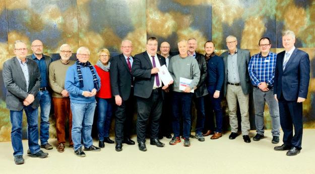 Das Bild zeigt Staatssekretär Mark Weinmeister in der Mitte. Links neben ihm der Erste Kreisbeigeordnete Jürgen Kaufmann, der erste Vorsitzende Bernd Knauf (mit Schild), ganz rechts Bürgermeister Klemens Olbrich. Foto: Hessische Staatskanzlei