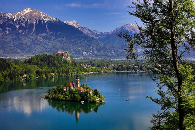 Der slowenische Luftkurort Bled. Auf der Insel liegt die Wallfahrtskirche Mariä Himmelfahrt, auf dem Felsen dahinter ist die im 11. Jahrhundert errichtete Burg Bled zu sehen. Foto: WGT e.V. | Heine