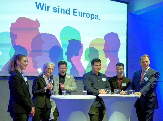 »Was bedeutet Europa für Jugendliche?« In der Talkrunde (v.li.): Wiktoria Dominiak (Hch. Kördel GmbH, Guxhagen / Polen), IHK-Hauptgeschäftsführerin Sybille von Obernitz, Winfred Yoel Manrique Boente (Fehr Dienstleistungs GmbH, Lohfelden / Spanien), Robin Müller (Viessmann Werke, Allendorf/Eder / Deutschland), Edoardo Deiana (tripuls media innovations gmbh, Marburg / Italien) und IHK-Präsident Jörg Ludwig Jordan. Foto: IHK