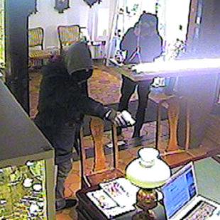 Einer der Täter bedroht die Angestellte. Foto: Polizei