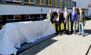 Landrat Winfried Becker gibt das Zeichen zur Enthüllung des neu gestalteten Quaders am Schuleingang. Foto: nh