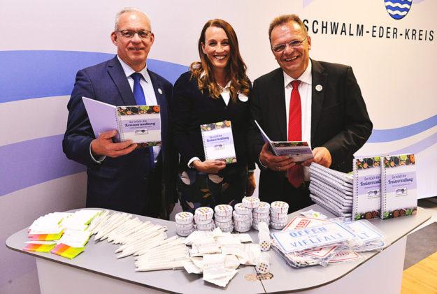 Erster Kreisbeigeordneter Jürgen Kaufmann, WIR-Koordinatorin Adriana Reitz und Landrat Winfried Becker freuen sich gemeinsam über das gelungene Kochbuch (v.li.). Foto: nh