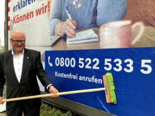Hessens Finanzminister Dr. Thomas Schäfer klebt in Wiesbaden ein Plakat mit dem Hinweis auf die neue Servicenummer. Foto: HMdF