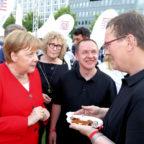 Klaus Vogt und Sven Metzner (v.re.) servieren Bundeskanzlerin Angela Merkel beim Hessenfest in Berlin eine »Für Uns«-Currywurst aus der Hephata-Metzgerei Alsfelder Biofleisch. Foto: Hephata