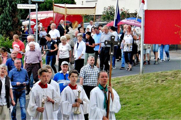 Messdiener und Gläubige der Pfarrgemeinde folgen der Prozession durch die Franz-Gleim-Straße. Foto: nh