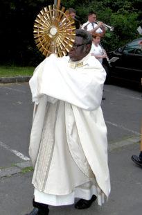 Pfarrer Josef Nzati Mabiala trägt die Monstranz vor dem Festzug her. Foto: nh