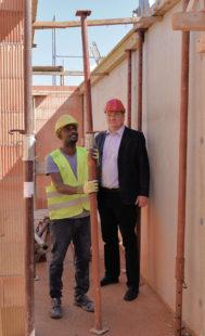 Ali Abdi stellt Stützen auf einer Sippel-Baustelle, Sozialverwalter Lars Werner schaut zu. Foto: nh