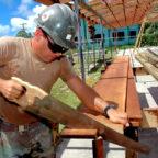 Im Ferienjob sägt ein Student auf einer Baustelle Bretter zurecht. Foto: skeeze | Pixabay