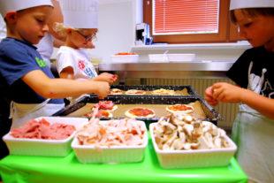 Bela, Nala und Ben Luca belegen kleine Pizzen mit ihren Lieblingszutaten (v.li.). Foto: Hephata