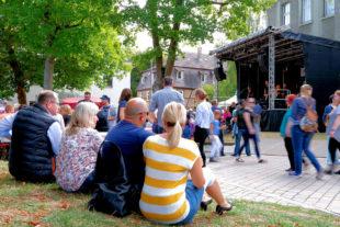 Schattiges Plätzchen: Unter den Bäumen neben der Hephata-Kirche können Besucher ganz entspannt dem Programm auf der Biodorf-Bühne lauschen. Foto: Stefan Betzler | Hephata