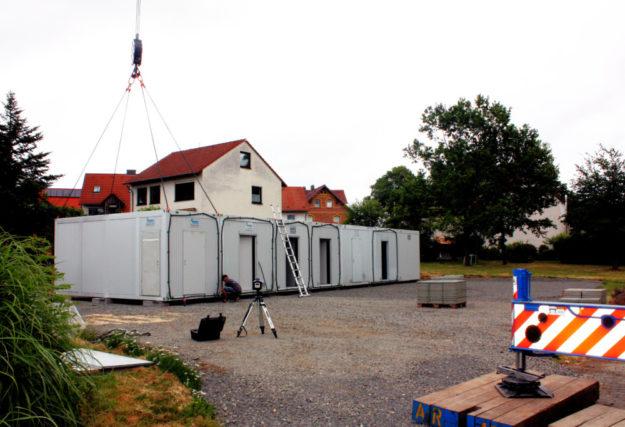Mit einem Kran werden die 19 Container der provisorischen Kita in der Fritzlarer Straße auf den Platz gehoben. Foto: nh