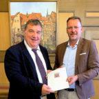 Mark Weinmeister (CDU) übergibt fünf Förderbescheide an Melsungens Bürgermeister Markus Boucsein. Foto: nh