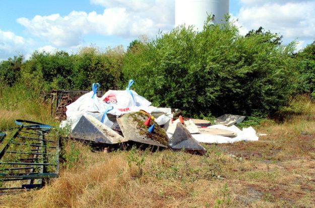 Die verwitterten und bemosten Teile der alten Minigolfanlage wurden in unmittelbarer Nähe zur Windkraftanlage in die Natur geworfen. Foto: Polizei