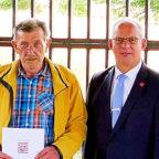 Wolfgang Schütz bekam von Erstem Kreisbeigeordneten Jürgen Kaufmann den Ehrenbrief überreicht. Foto: nh