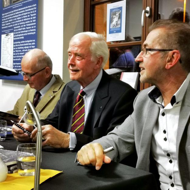 Zahlreiche Buchexemplare durften (v.li.) Hans-Hayo Hayessen, Volker Hayessen und Dr. Dieter Vaupel nach dem Ende der Veranstaltung signieren. Foto: Erika Mönig
