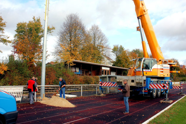 Mitarbeiter des Bauunternehmens Fröde aus Homberg stellen einen der Flutlichtmasten auf. Foto: nh