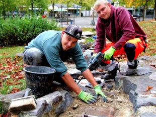 Daniel Heilig (li.) und Christoph Schöps entfernen einige brüchig gewordene Betonstücke in dem künstlich angelegten Bachlauf. Foto: Klein