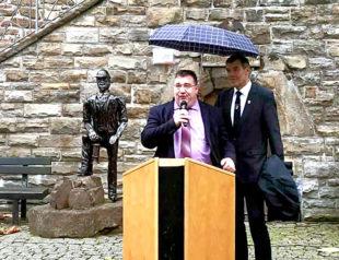 Europastaatssekretär Mark Weinmeister hält eine Ansprache zur Bescheidübergabe, Fritzlars Bürgermeister Hartmut Spogat hält den Schirm. Foto: nh