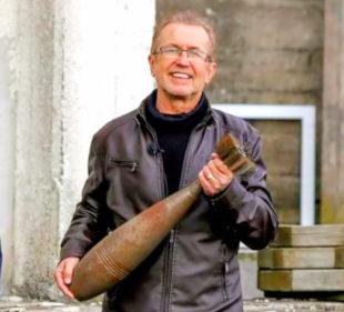 Dr. Dieter Vaupel hat eine Bombe, die aus Hirschhagen stammt, in der Hand und erläutert vor einem ehemaligen Produktionsgebäude die Arbeitsbedingungen unter denen Blanka und die anderen Frauen leiden mussten. Foto: Karnebogen | nh