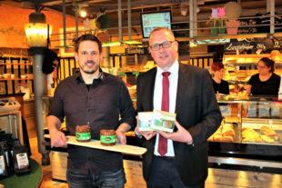 """Backhaus-Chef Christoph Schwarz (li.) und Bürgermeister Frank Börner mit zwei innovativen Produkten: Das Vitalkornbrot (auf dem Brett) und das ausschließlich aus Gemüse und Saaten hergestellte """"Broot"""" enthalten kein Mehl. Foto: nh"""
